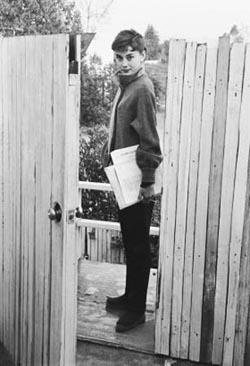 Audrey Hepburn waits by the gate of her apartment for the studio car. She was on the set of Sabrina by 6:30 every morning. (Photo by Mark Shaw)