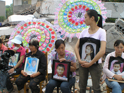 Grieving parents wait with pictures of their dead children for answers from government officials  about the shoddy construction of the school buildings. (Photo courtesy of HBO)