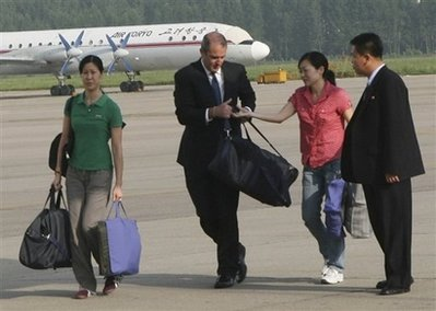 In this photo released by China's Xinhua News Agency, the two female American journalists, far left, and second right, head to a chartered plane carrying the homebound former President Bill Clinton at an airport in Pyongyang, capital of North Korea Wednesday, Aug. 5, 2009. His mission accomplished, former President Bill Clinton left Pyongyang early Wednesday accompanied by American journalists Euna Lee and Laura Ling after North Korean leader Kim Jong Il pardoned the women from their 12-year prison sentences. (AP Photo/Xinhua, Zhang Binyang)