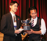 "Albert Lee, AAJA Professional Programs Coordinator, presents freelance photographer Kelvin Ma with the Dith Pran perpetual trophy and a cash award for his winning entry ""Free Hug"", in the Annual Dith Pran Photography and Multimedia ShootOut Competition. © Lia Chang"