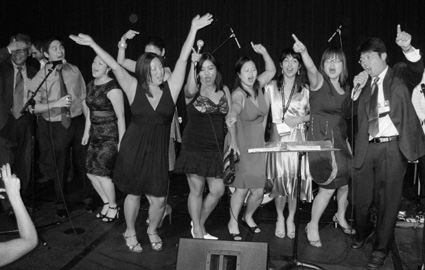 "New England Chapter sings ""Sweet Caroline,"" at the AAJA karaoke night, accompanied by live band Nickel and Dime on August 15, 2009. (L-R) Kim Tan, Phil Marcelo, Susan Choi, Tracy Jan, Hanah Fadrigalan, Shirley Goh, Sangita Chandra, Shirley Leung, and Daigo Fujiwara.© Lia Chang"