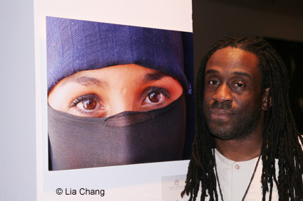 Will Calhoun poses with a photograph he created during his travels, after his performance at the Chelsea Art Museum on October 28, 2009. © Lia Chang