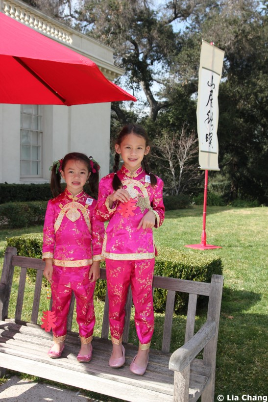 Alexandra Bertolini (age 4) and Angelina Bertolini ( age 6) in their Chinese New Year finery, display their papercuts-the Chinese character for Spring, at the Chinese New Year Festival at The Huntington in San Marino. Photo by Lia Chang