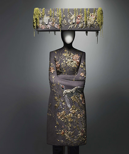 Alexander McQueen (British, 1969–2010), Ensemble, VOSS, spring/summer 2001,  Jacket of pink and gray wool bird's-eye embroidered with silk thread; trouser of pink and gray wool bird's-eye; hat of pink and gray wool bird's-eye embroidered with silk thread and decorated with Amaranthus, Courtesy of The Metropolitan Museum of Art, Photograph © Sølve Sundsbø/Art + Commerce