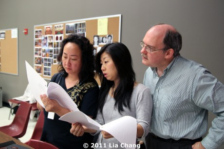 Translator Candace Chong (center) reviews the Chinese dialogue in the new script pages with Joanna C. Lee and Ken Smith, Cultural Advisors for Chinglish, in the Healy Room of the Goodman Theatre in Chicago on June 5, 2011. © 2011 Lia Chang