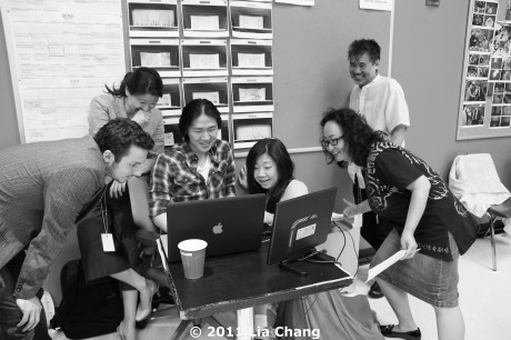 """(L-R) Actors Stephen Pucci, Angela Lin, Projection Designer Shawn Duan, Translator Candace Chong, Cultural Advisor Joanna C. Lee and playwright David Henry Hwang are in stitches watching a video from CHINA'S GOT TALENT: a foodseller singing about her """"free scallions"""" to a tune from the opera TURANDOT. © 2011 Lia Chang"""