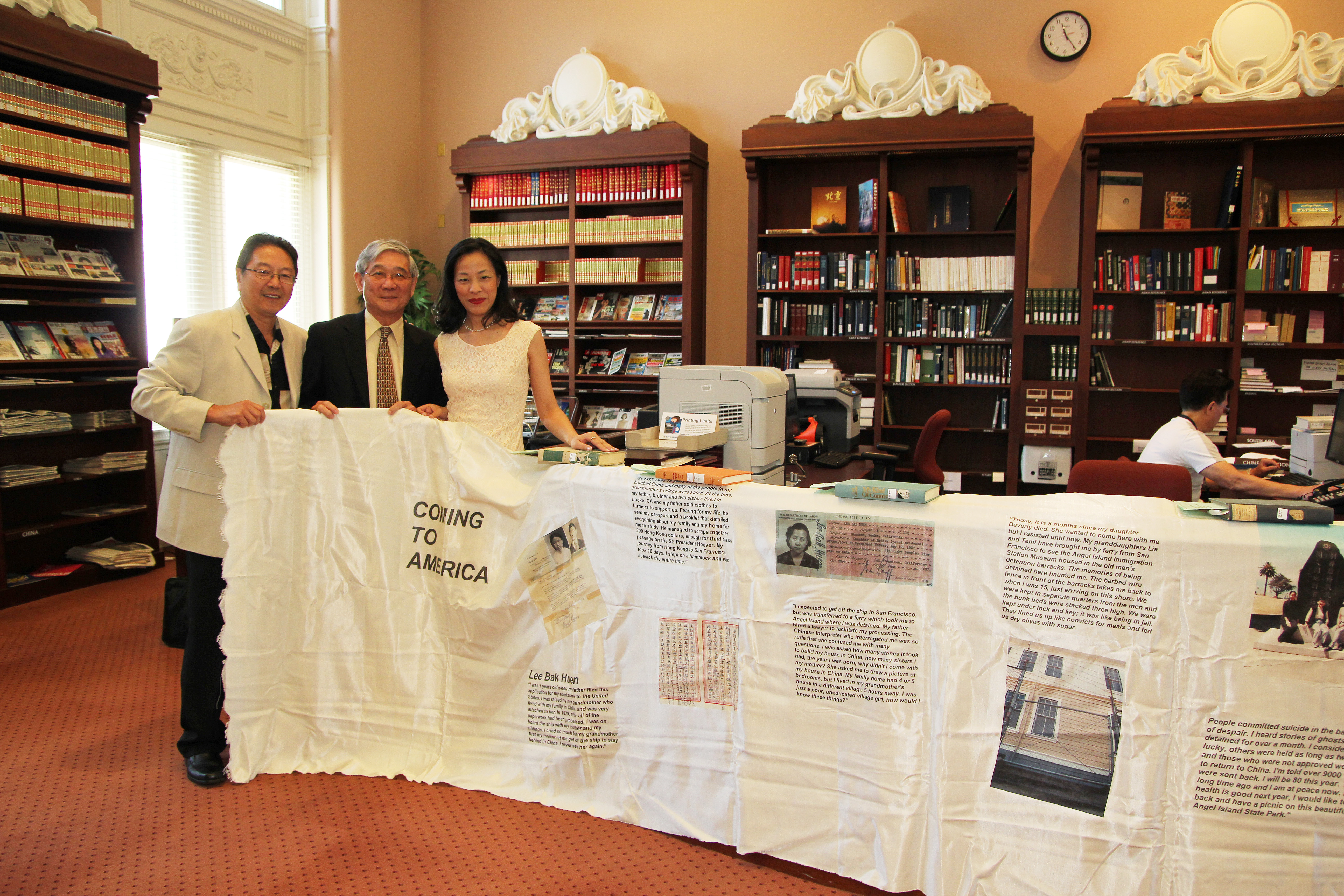 """Rick Shiomi, playwright and artistic director of Mu Performing Arts, Franklin Odo, chief of the Asian Division of the Library of Congress, and artist Lia Chang display """"Coming to America"""", Chang's Fabric Book Art Installation in the Asian Reading Room of the Library of Congress in the Thomas Jefferson Building in Washington D.C. on July 27, 2011. Photo by Reme Grefalda"""