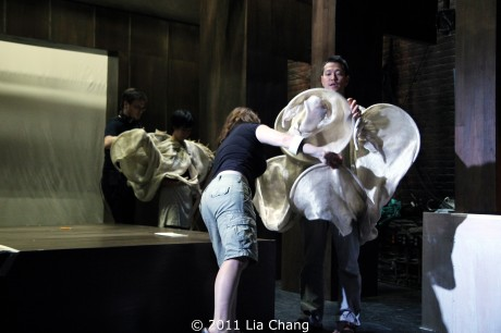 Stage manager Joanne E. McInerney helps Louis Ozawa Changchien with his costume. Photo by Lia Chang