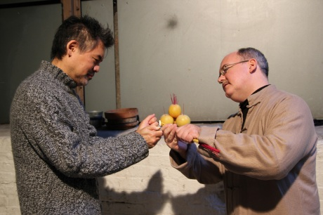 Playwright David Henry Hwang and Chinglish cultural advisor Ken Smith light the incense for the altar which is set up in the theater alley on the way to the stage door.  Photo by Lia Chang