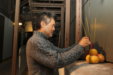 Playwright David Henry Hwang places incense in the altar for good fortune. Photo by Lia Chang