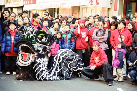 Black lion costume and spectators during Chinese New Year Parade, New York Chinatown, 2002. (Lia Chang)