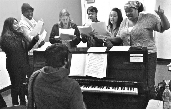 """BUMBUG The Musical GET ON THE TRAIN musical rehearsal"" (From Left to Right) -Falu (CRATCHEETA), Kiarri D. Andrews (ENSEMBLE), Matthew Knowland (ENSEMBLE), Debargo Sanyal (BHAVESH), Brooke Ishibashi (ENSEMBLE), Adrienne C. Moore (ANGEL) -Samrat Chakrabarti at the piano. Photo by Katie Rosin."