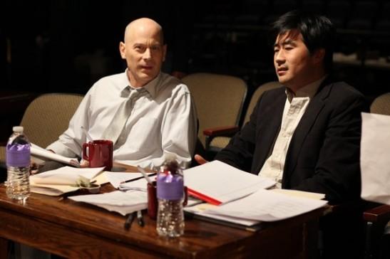 "Playwright DHH (Ryun Yu) and theater producer Stuart Oslow (Michael Krawic) discuss DHH's latest play ""Face Value"". Photo credit: Ozum Bobaroglu"
