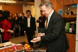 Signature Theatre Founding Artistic Director Jim Houghton is the first to sample the roast pig. Photo by Lia Chang