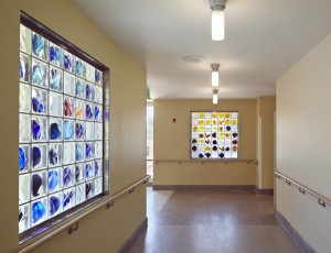 "Arlan Huang created a series of glass panels, approximately 4' x 5', on which he mounted his signature hand-blown glass ""stones"" inserted into glass blocks. The stones, which glow like jewels, were created in New York and assembled in the glass blocks at Dorothy Lenehan Studios in Oakland. Photo by: Bruce Damonte‬ Location: Connector Building between the Pavilion and North Residence"