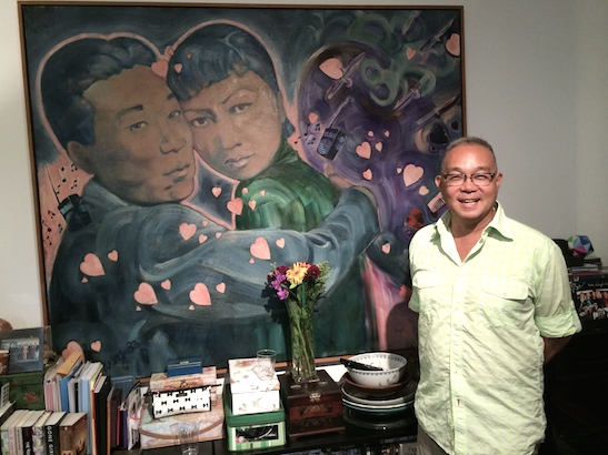 """Arlan Huang poses in front of his painting, """"Let's Do It, Let's Fall in Love"""" of Philip Ahn and Anna May Wong, at the home of Marilynn K. Yee and George Chew on September 13, 2014. Photo by Lia Chang"""
