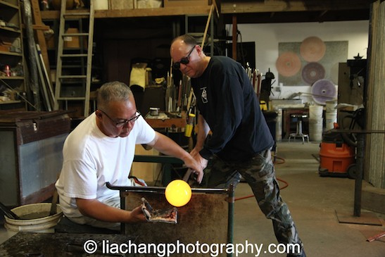Arlan Huang and Kevin Scanlan shaping the glass piece. Photo by Lia Chang