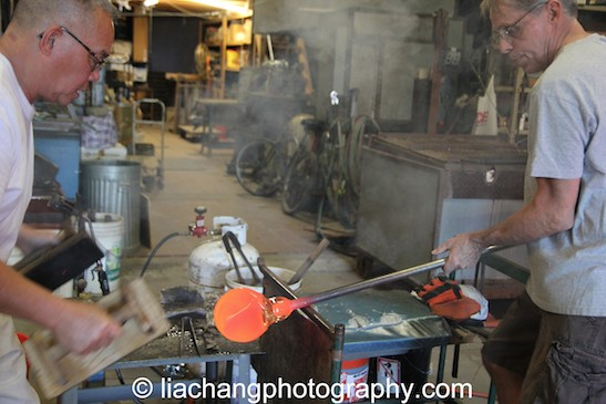 Arlan Huang shapes the glass piece, while John Brekke rotates it. Photo by Lia Chang