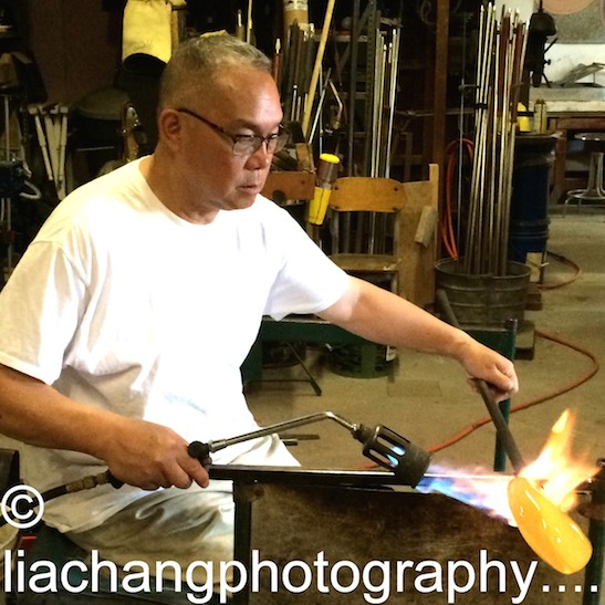 Arlan Huang uses a blow torch on the glass piece. Photo by Lia Chang