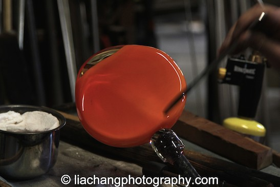 Arlan Huang cracks the piece off of the pipe using a wooden block to tap the pipe forcefully. Photo by Lia Chang
