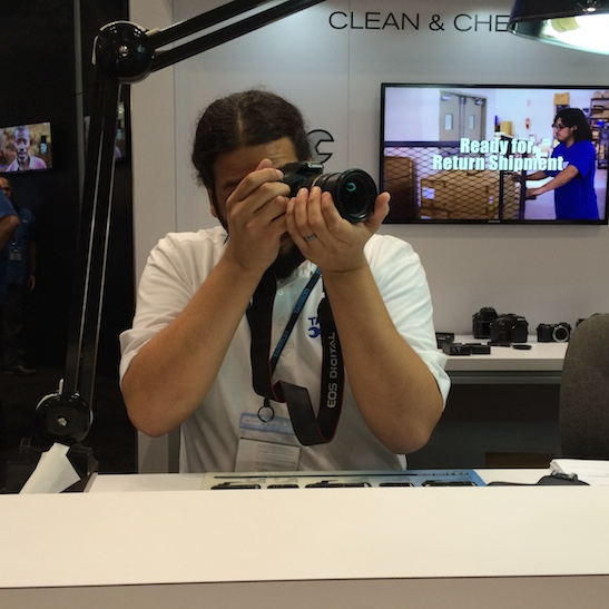 Rick inspects and cleans my lens at the Tamron booth at the PhotoPlus Expo at the Jacob Javits Center in New York on October 31, 2014. Photo by Lia Chang