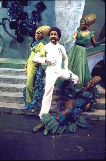 """Actor André De Shields (C) w. cast in a scene fr. the Broadway musical """"The Wiz"""". (c.1974) Photo by Martha Swope courtesy of THE NEW YORK PUBLIC LIBRARY DIGITAL COLLECTIONS"""