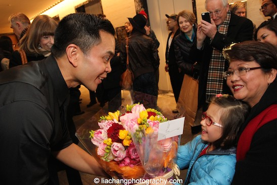 Jose Llana receives flowers from his niece, Veronica. Photo by Lia Chang