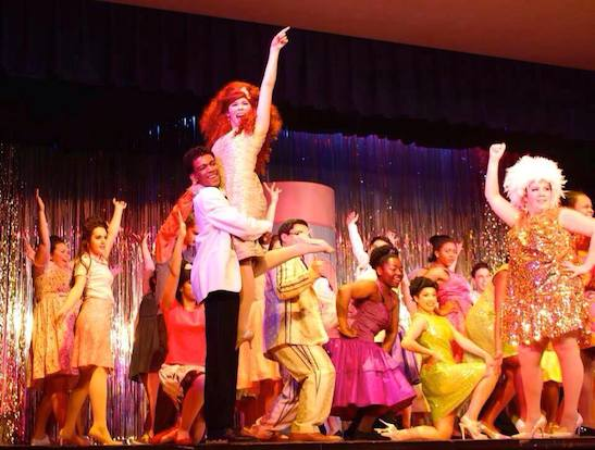 Kyra Bowes as Penny Pingleton (center in the red wig) and the cast of HAIRSPRAY. Photo courtesy of Leslie Yngojo-Bowes