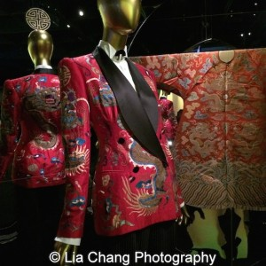 An ensemble by Ralph Lauren from 2011–12 - Jacket of red silk shantung and black silk satin embroidered with polychrome silk and gold metallic thread; shirt of white cotton broadcloth; pants of black and white pinstriped wool-synthetic twill; Chinese Theatrical costume Made during and Red silk satin brocaded with polychrome silk thread, Courtesy of the Palace Museum, Beijing.