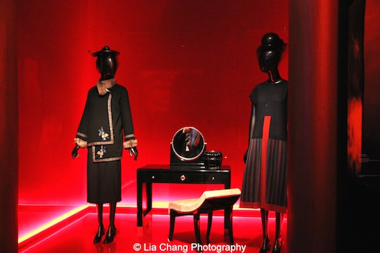 """A 1912 Paul Poiret """"Steppe"""" coat of Black wool embroidered with blue, white, and gray silk thread; gray fox fur; a 1923 Paul Poiret """"Mademoiselle"""" dress of Black and red wool crepe with polychrome striped wool twill; Émile-Jacques Ruhlmann """"Chinoise"""" dressing table, ca. 1927 and a """"Retombante"""" stool, ca. 1916-18."""