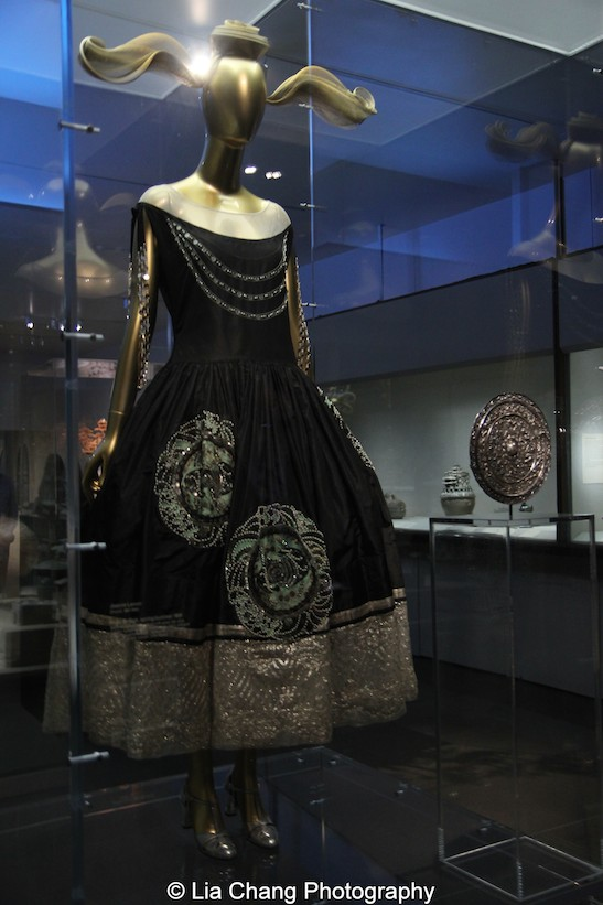 A 1924 Jeanne Lanvin Robe de Style of Black silk taffeta embroidered with green silk and silver metallic thread, and synthetic pearl, silver, black, and gold beads and paillettes; silver lamé and ivory silk tulle embroidered with metallic silver thread; Chinese Mirror, Tang Dynasty (618 – 907), 8th century Silver.