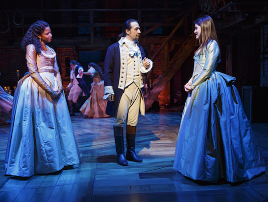 Renée Elise Goldsberry plays Angelica Schuyler, Lin-Manuel Miranda plays Alexander Hamilton, and Phillipa Soo plays Eliza Hamilton in Hamilton. (© Joan Marcus)