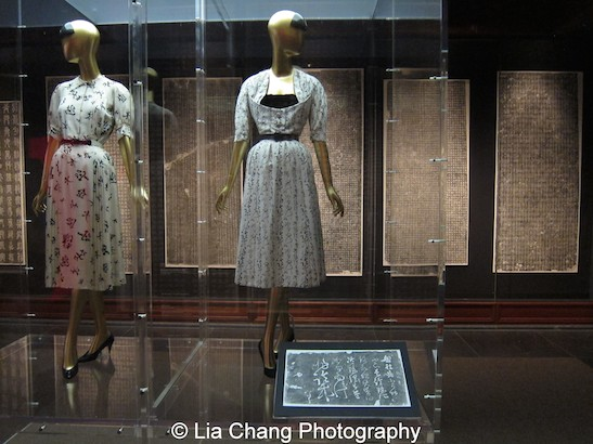 "(L-R) Gabrielle ""Coco"" Chanel (French, 1883–1971) Dress, ca. 1956 White silk surah printed with black Chinese character motifs Brooklyn Museum Costume Collection at The Metropolitan Museum of Art, Gift of the Brooklyn Museum, 2009; Gift of H. Gregory Thomas, 1959 (2009.300.261a–c); Christian Dior (French, 1905–1957) ""Quiproquo"" cocktail dress, 1951 White silk shantung printed with black Chinese character motifs Gift of Mrs. Byron C. Foy, 1953 (C.I.53.40.38a–d). Zhang Xu (ca. 675–759); Letter about a Stomachache 19th-century rubbing of a 10th-century stone carving Ink on paper Seymour and Rogers Funds, 1977 (1977.375.31a). Photo by Lia Chang"