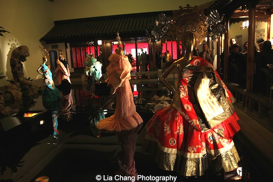 """Through the Looking Glass"" translates into Chinese as ""Moon in the Water."" In the Met's Astor Chinese Garden Court, a moon was projected onto the ceiling and reflected in what appears to be a shallow pool. Dresses by John Galliano and Martin Margiela—which appear like apparitions on the water—were inspired by Beijing opera. Photo by Lia Chang"