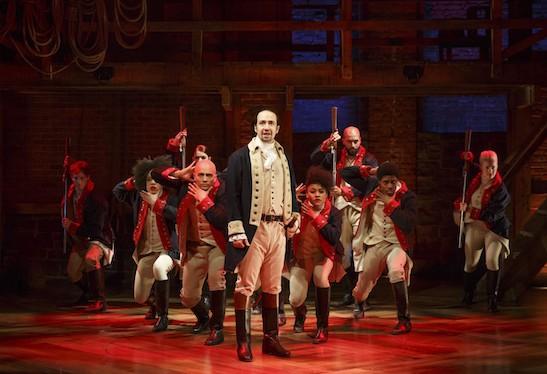Lin-Manuel Miranda, center, and the cast of Hamilton. Photo by Joan Marcus