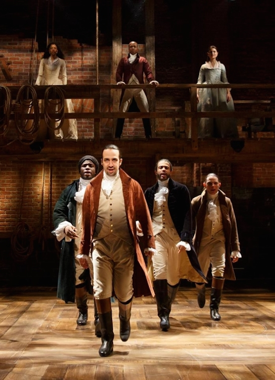 Lin-Manuel Miranda, center, and the cast of Hamilton. Photo by Joan Marcus