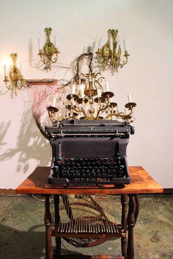 David McQueen …the flooding sunshine, the fire of big logs, the white expanse of cushioned snow and the incomparable river., 2015 Vintage chandelier and sconces, re-purposed Underwood typewriter, momentary switches, brass, wood, wire 14' x 4' x 6' Courtesy of the artist and Kim Foster Gallery
